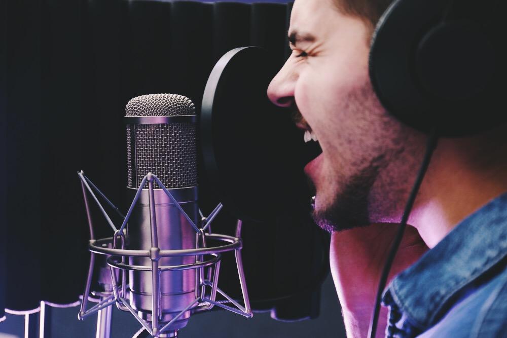 Homme en train de chanter avec émotion dans un micro